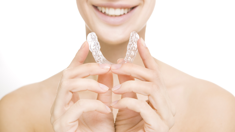 Dental patient holding up a tray of Invisalign Clear Braces near 34135