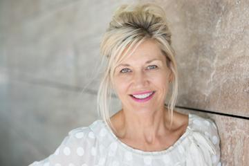 a woman smiles, leaning against a wall | bonita springs tooth colored fillings