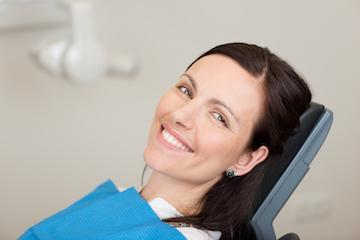 a woman smiles in the dental chair | bonita springs periodontal care