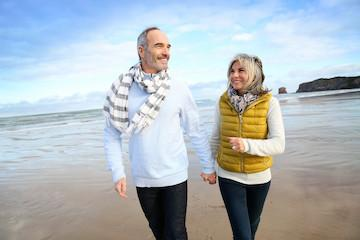 a middle aged couple walks on a beach | bonita sprigs crowns and bridges