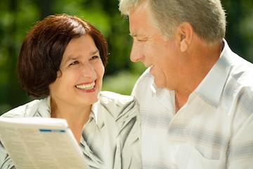 a couple looks at a news paper | bonita springs full and partial dentures