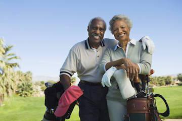 an elder couple smiles on a golf course | full and partial dentures bonita springs