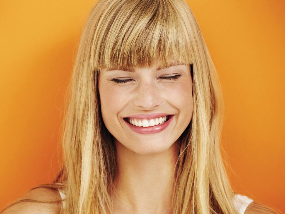 Patient against an orange wall smiling after Invisalign treatment in Bonita Springs