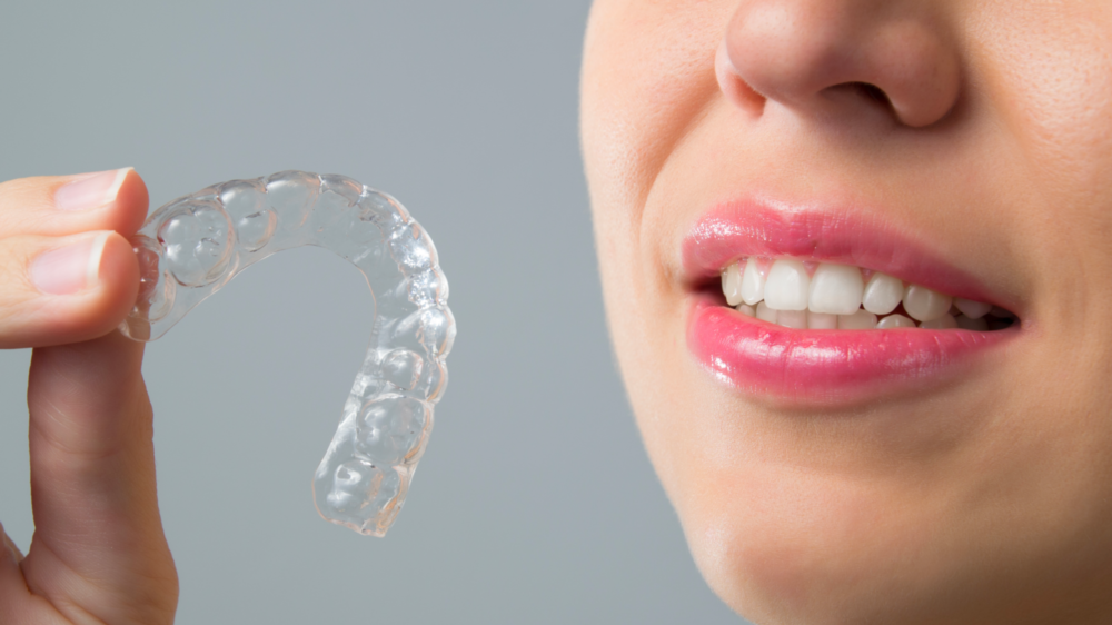 Woman holding up Invisalign clear braces near North Naples, FL