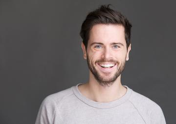 a man smiles in front of a grey backdrop | comfortable dentistry bonita springs
