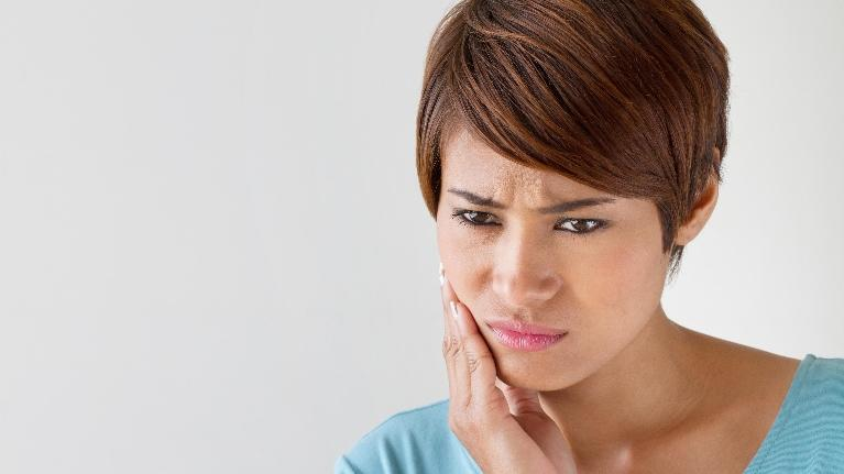 A woman holds her hand to her jaw | Dental Crowns Bonita Springs FL