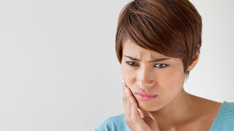 Root Canals Bonita Springs | A woman holds her jaw in pain