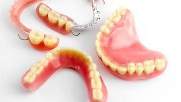 full and partial dentures sit on a white backdrop | dentures in bonita springs