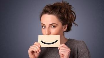 bonita springs dentist | woman holding sign in front of her with a smile on it