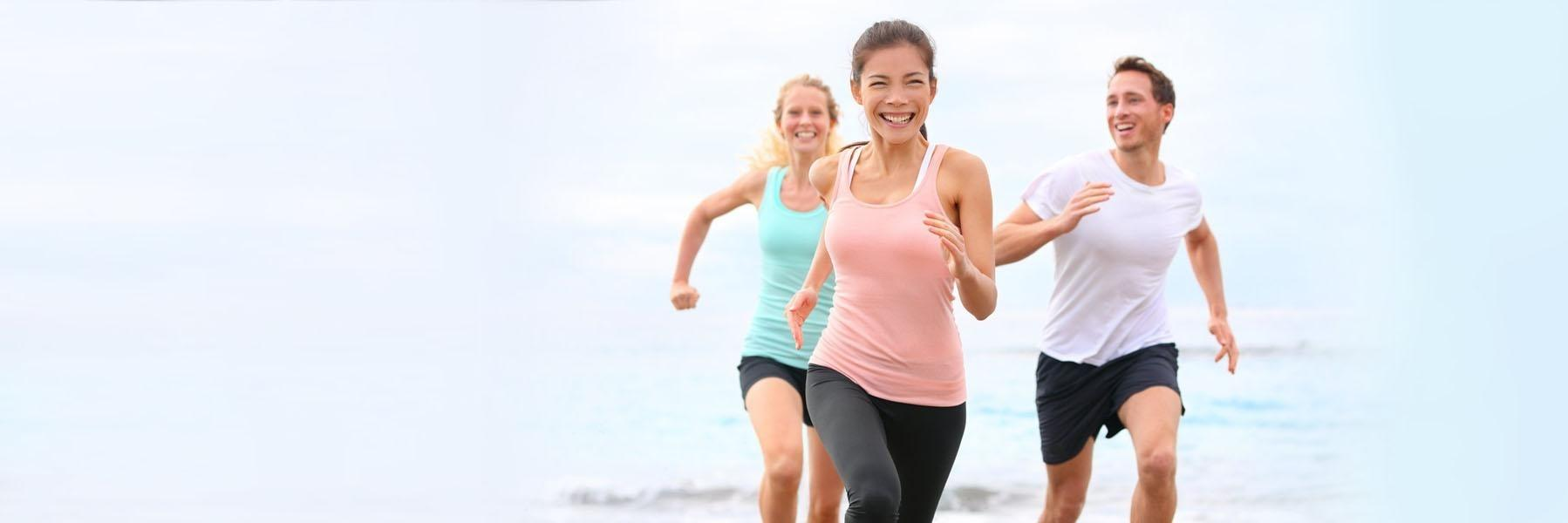 Woman wearing Invisalign while running on the beach near 34135